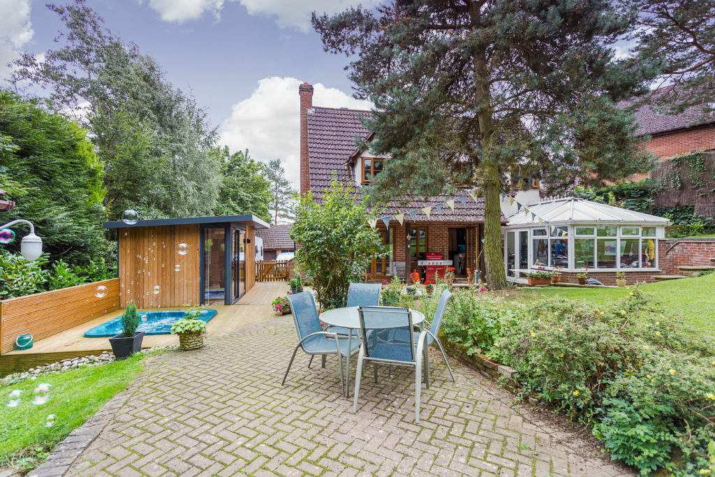 Exterior of a house with a large tree in front and a conservatory attached to the right hand side, a garden furniture set and a TGO1 to the left with bubbles floating on the left
