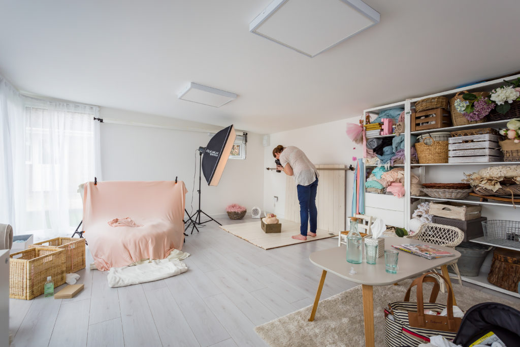 Interior of TGO1 photography studio with storage against the wall filled with props and the photographer taking a photo of a baby
