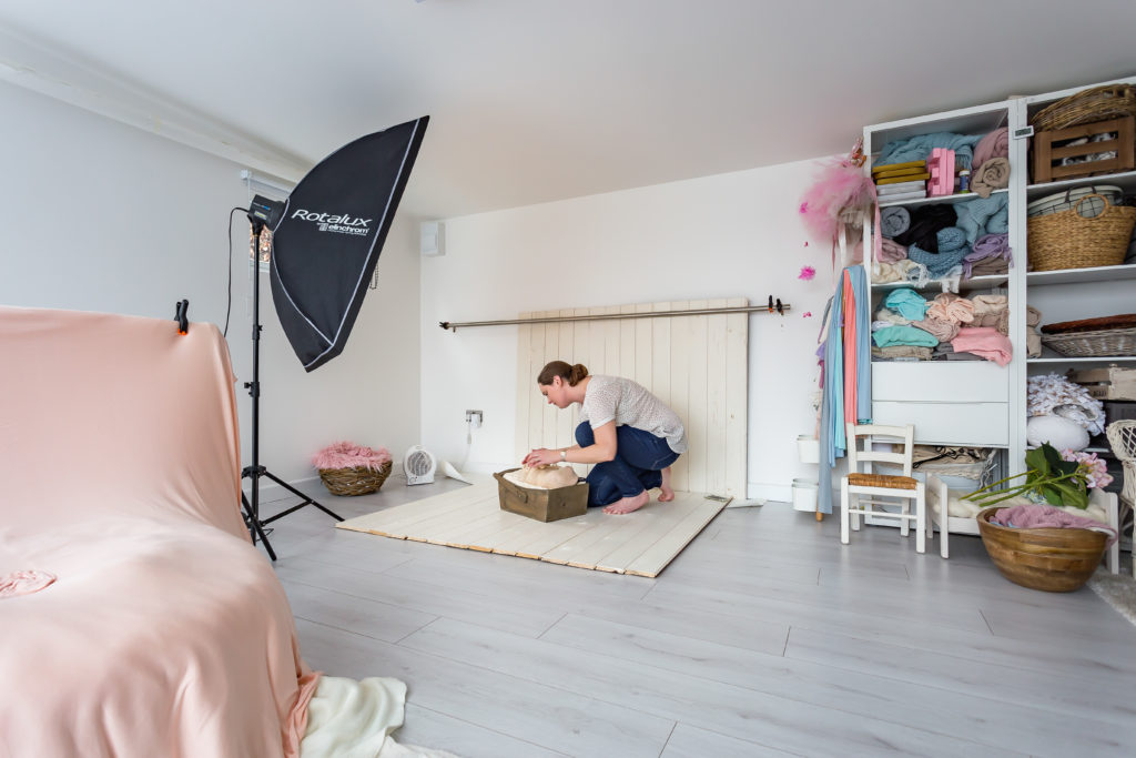 Interior of a TGO1 photography studio with the photographer crouched down in front of a baby and a set