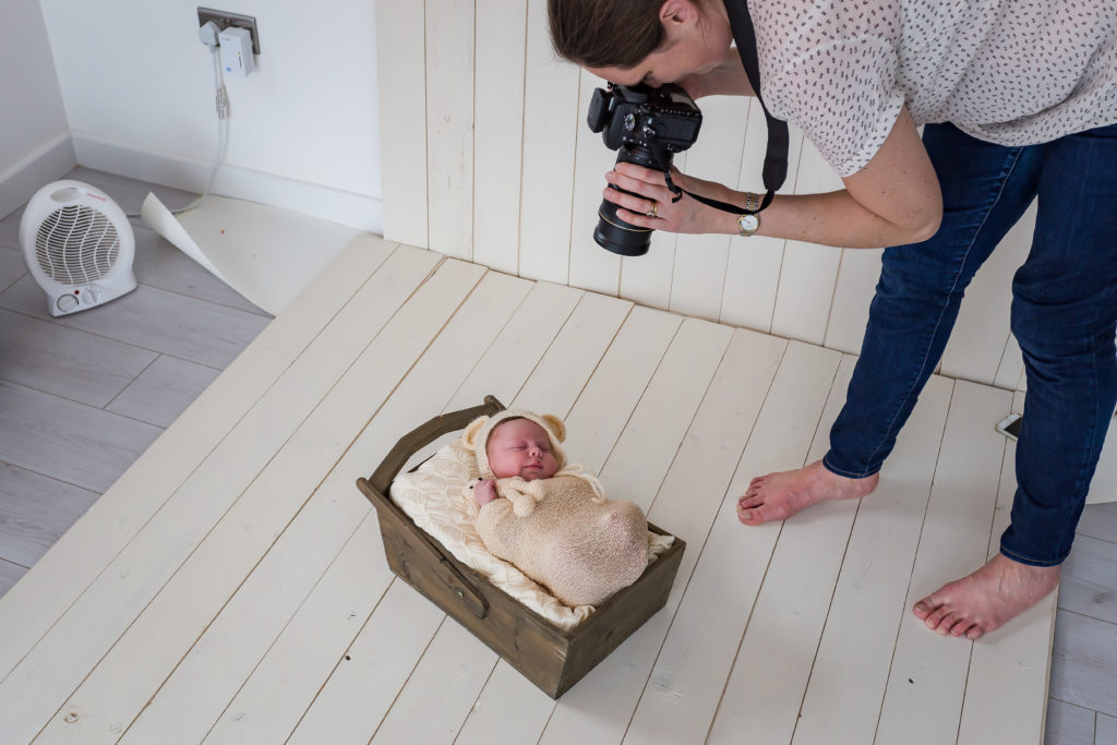 Swaddled baby in a basket with the photographer standing above and taking a photo