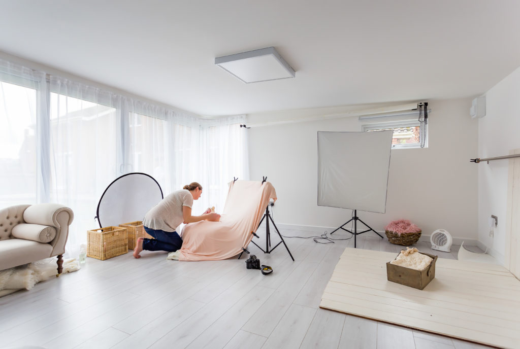 Interior of a TGO1 photography studio with the photographer crouched down in front of a swaddled baby