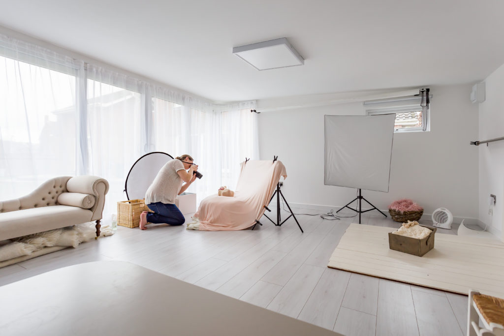 Interior of a TGO1 photography studio with the photographer crouched down in front of a swaddled baby and taking a photo