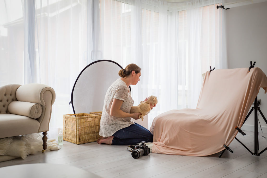 Interior of a TGO1 photography studio with the photographer holding a swaddled baby