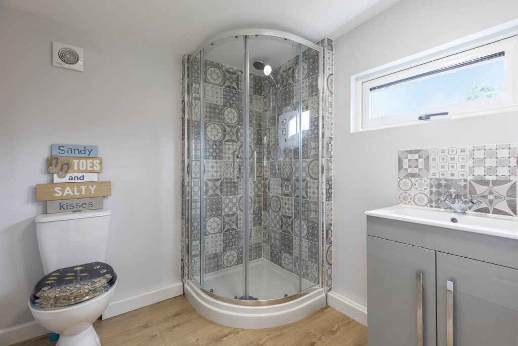 Small bathroom with toilet on the left, tiled shower in the centre and a sink on the right hand wall