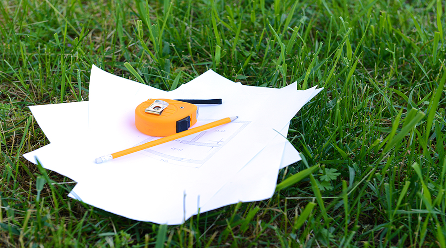 Paper on grass with a tape measure and pencil on top