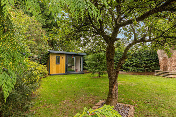 garden office surrounded by trees