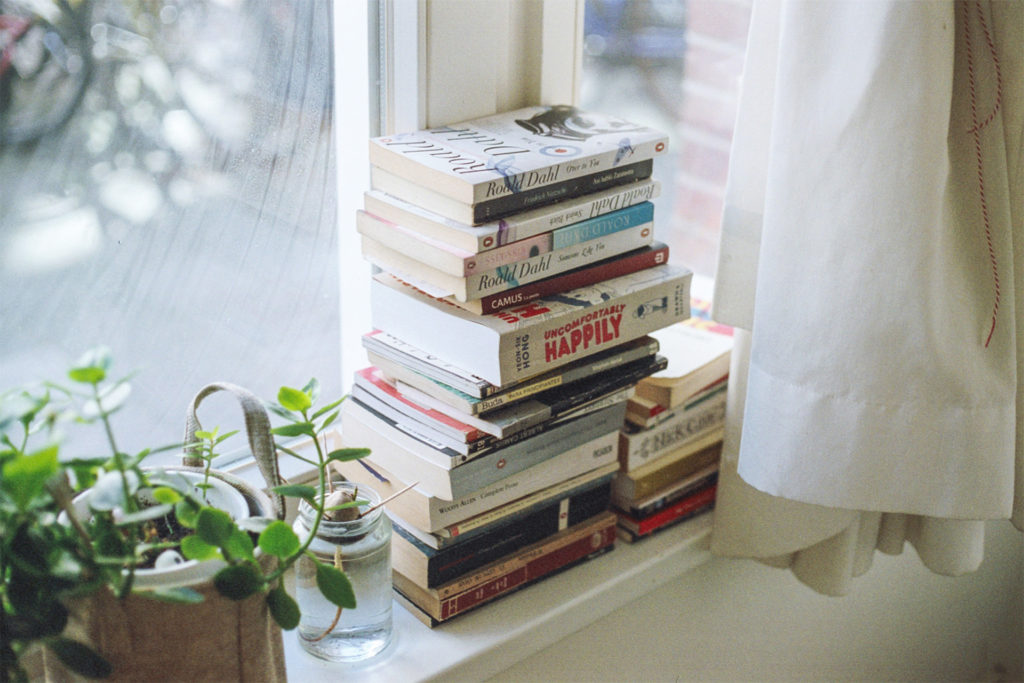 A stack of books on a window ledge