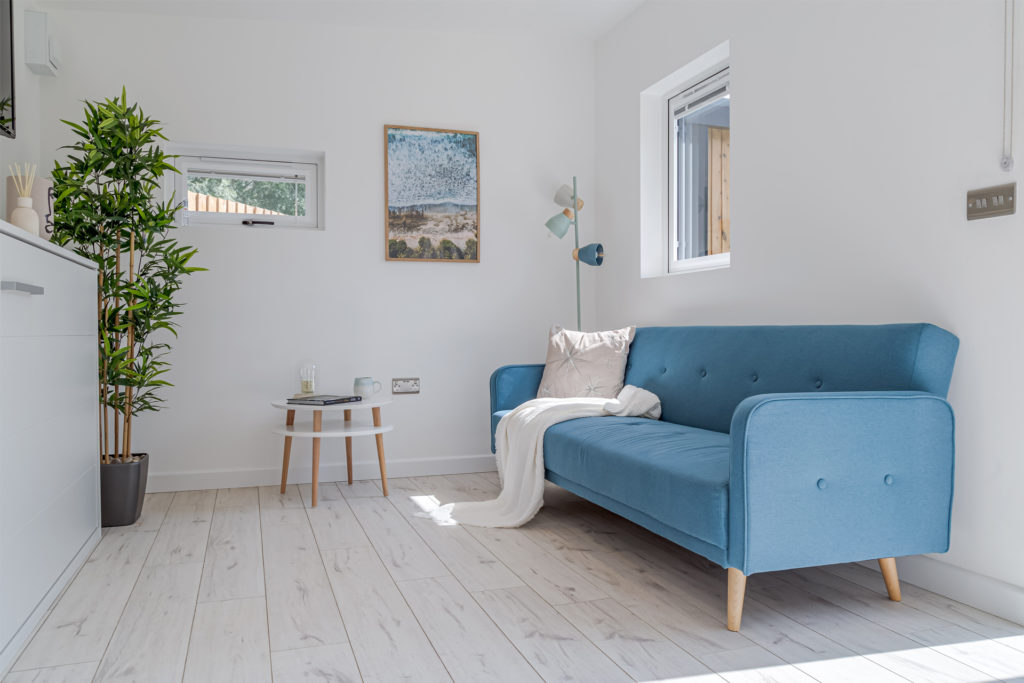Interior of an annex with blue sofa and a throw and cushion on it