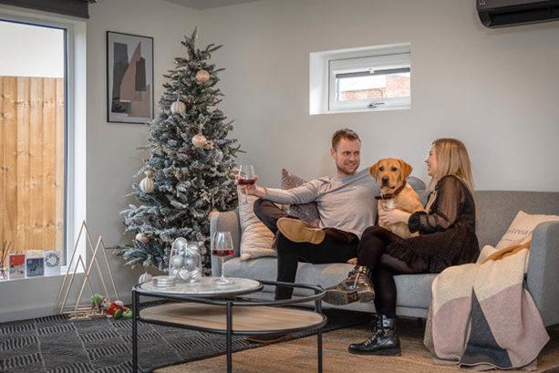 people and dog sat on sofa with christmas decor