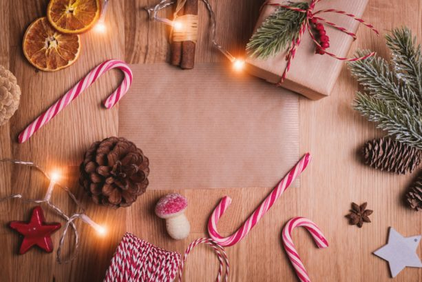 Christmas flat lay on wooden table with candy canes, dried oranges and presents