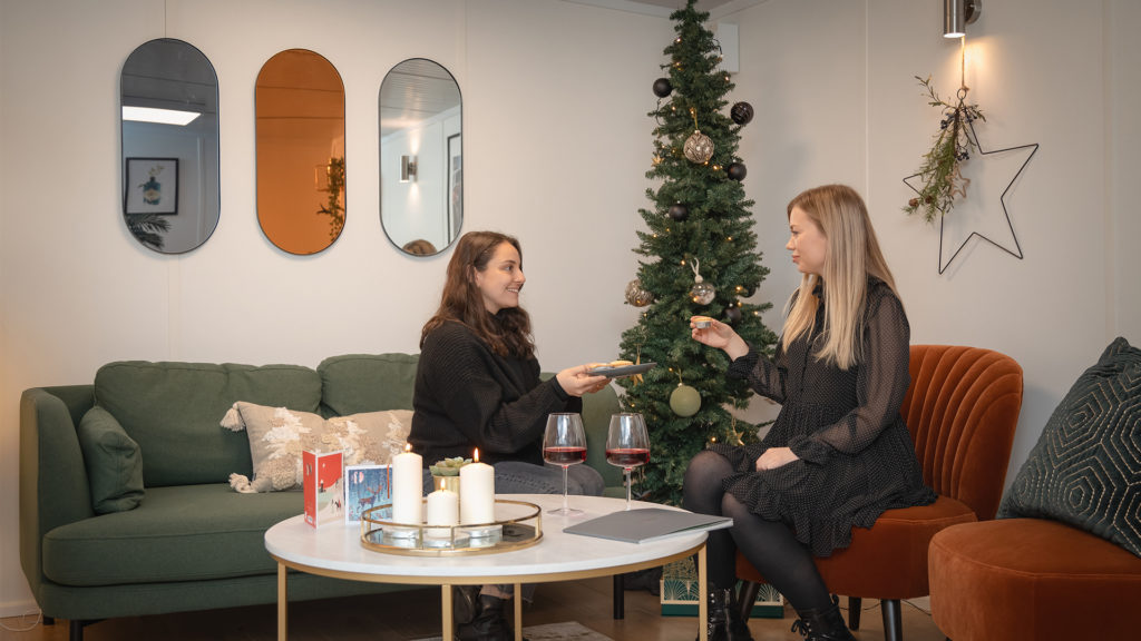 Two women enjoying mince pies in a room decorated for Christmas