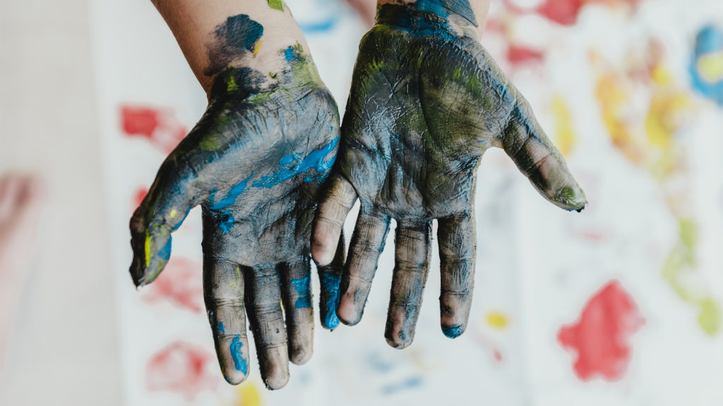 Childs hands covered in paint