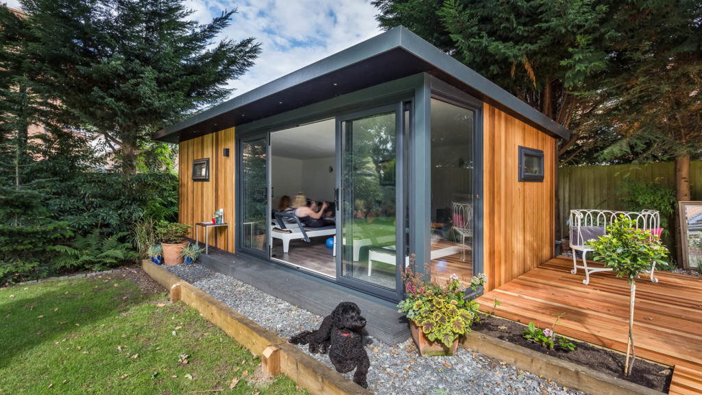 Exterior of home pilates studio with a black dog outside