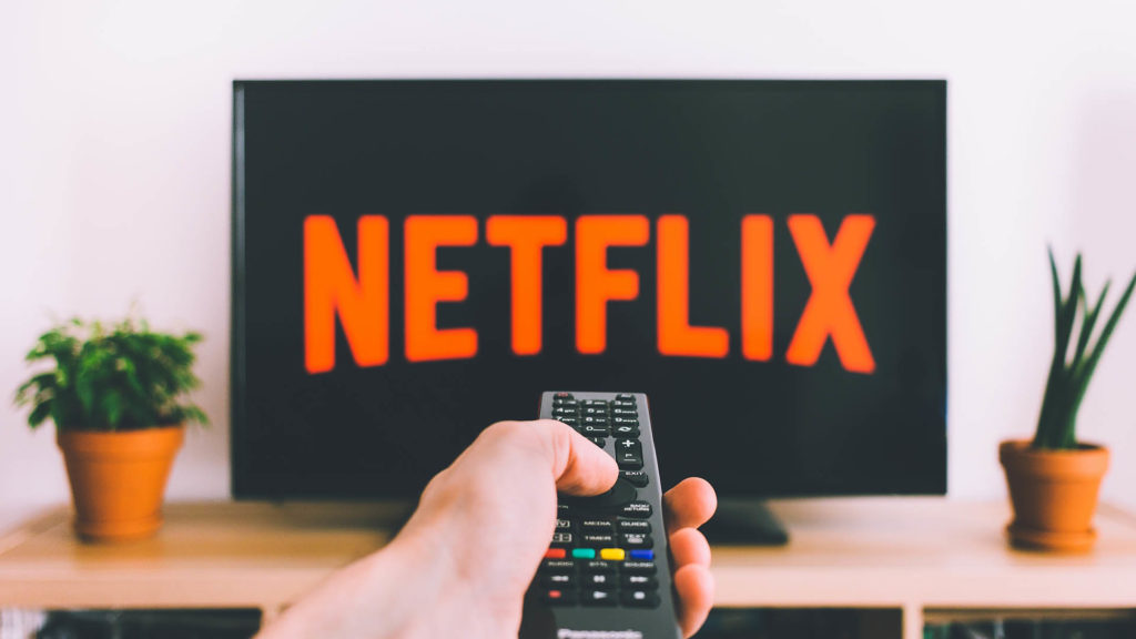 Someone pointing a remote directly at a TV with the Netflix logo showing