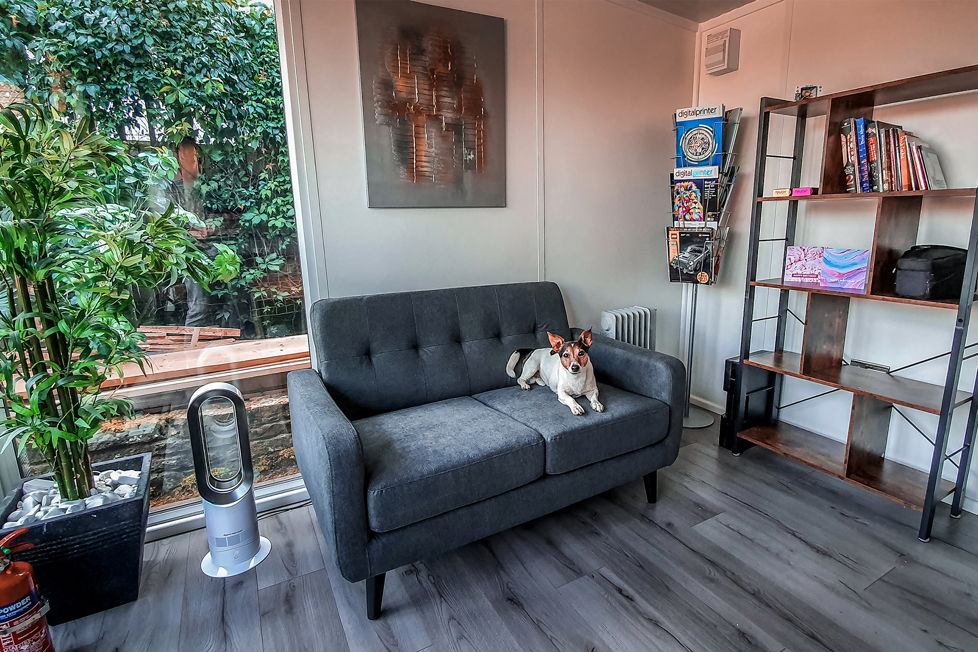 Interior of home garden office with a grey sofa and a jack russell