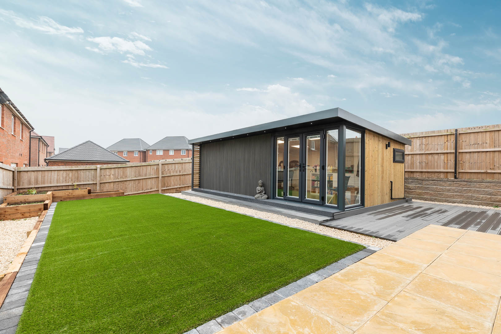 Side angle of a garden hair & beauty salon in a garden with a fence around it, astro turf and decking on top of paving