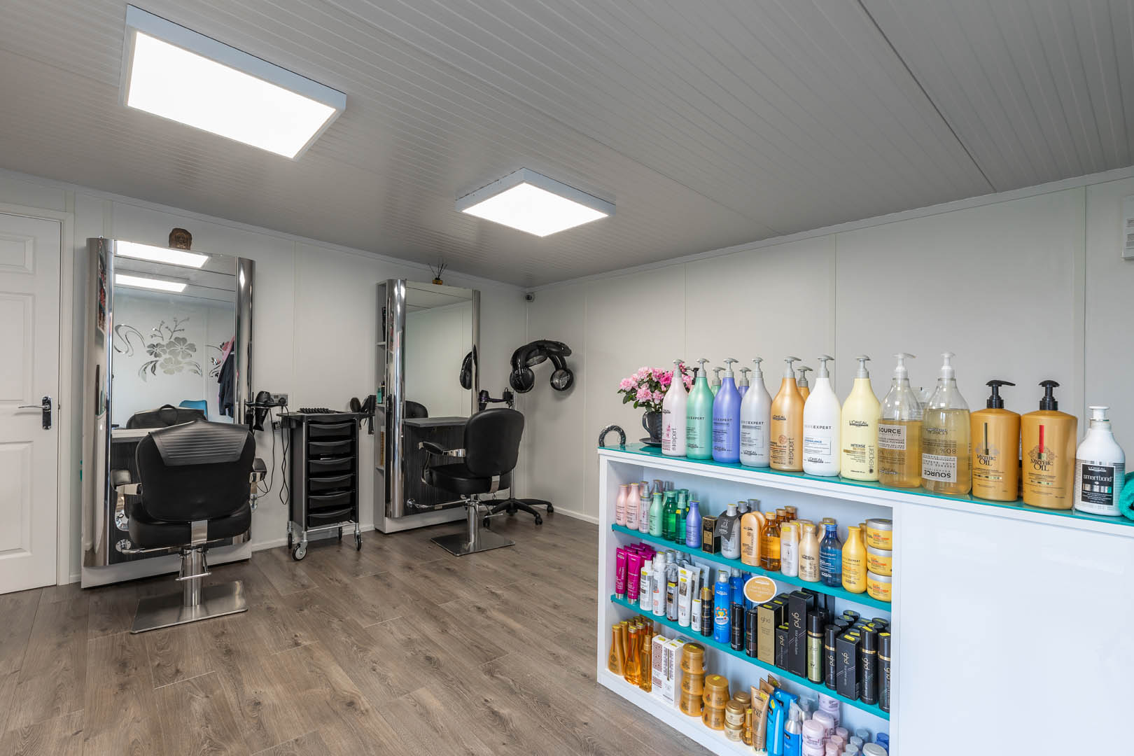 Interior of a garden hair & beauty salon with two salon chairs and mirrors to the left and a display cabinet to the right