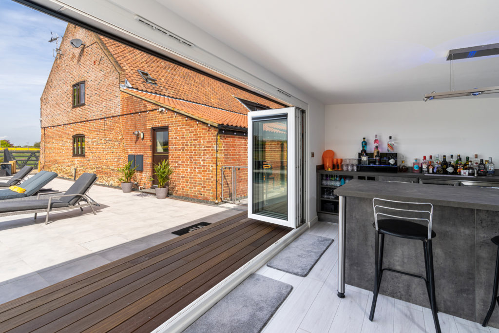 Interior of a home bar garden building looking out onto a patio and sun loungers.