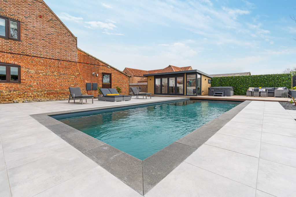 Exterior of a home bar garden building with sun loungers to the left, a hot tub and seating area to the right and a swimming pool in the foreground.