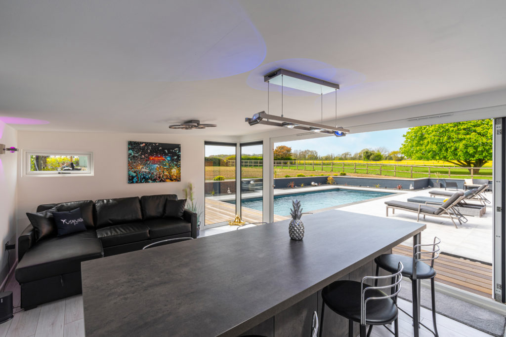 Interior of a home bar garden building looking out onto a pool, patio and sun loungers.
