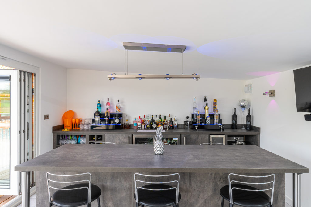 Interior of a home bar garden building with a bar and stools and alcohol on a sideboard.