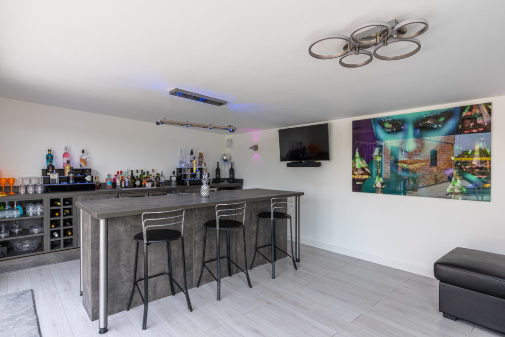 Interior of a home bar garden building with a bar and stools, alcohol on a sideboard, a wall on the right hand wall and a painting next to the TV