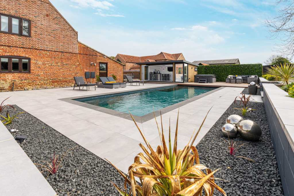 Exterior of a home bar garden building with sun loungers in the foreground. A hot tub sits to the right of the building and a pool in front.