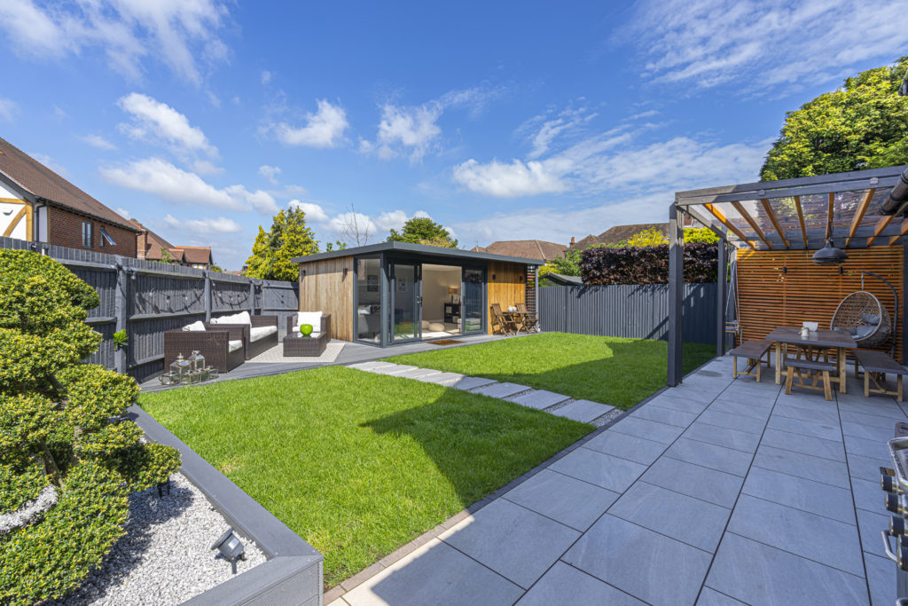 Exterior of a garden room on a patio with garden furniture to the left and a paved patio on the right