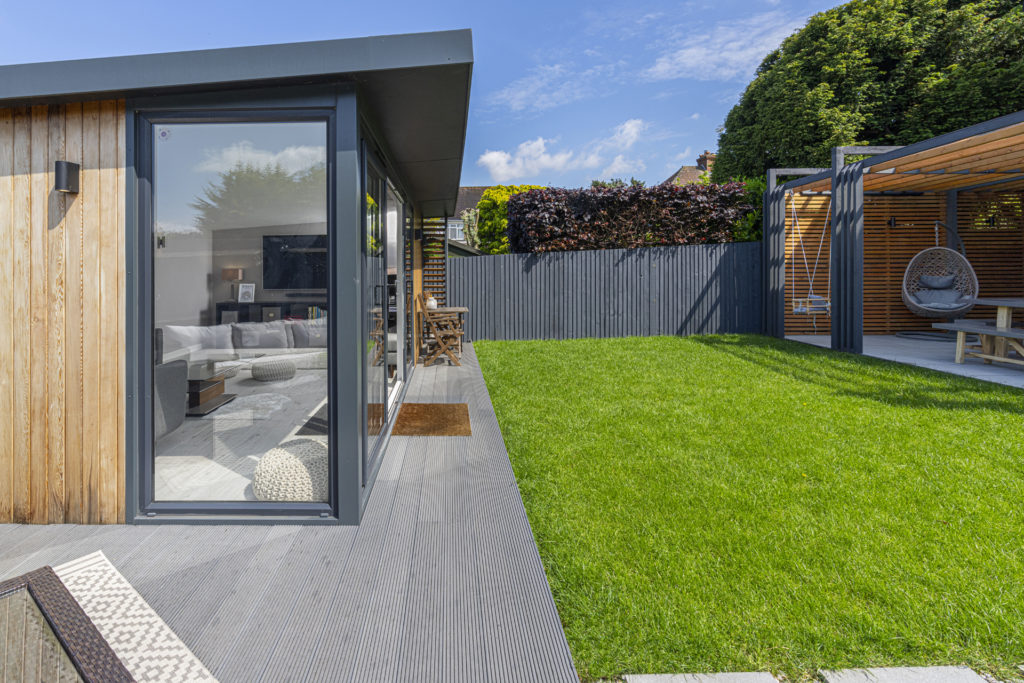 Exterior of a garden room with a bistro set at the front and a covered patio on the right hand side of the garden