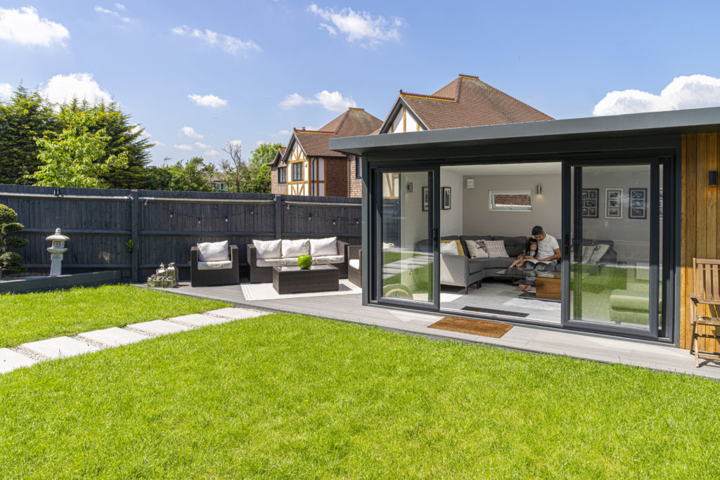 Exterior of a garden room on a patio with garden furniture to the left and a father and daughter sitting inside the garden room