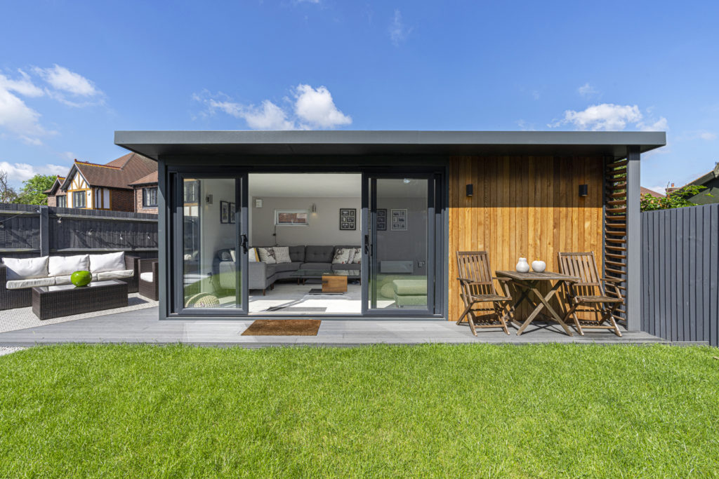 Exterior of a garden room on a patio with garden furniture to the left