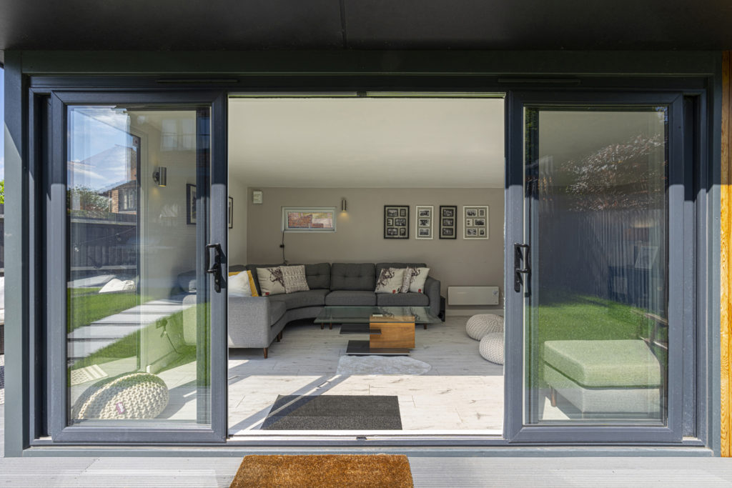 Exterior of a garden room with its doors open and an L shaped grey sofa inside with photos on the back wall