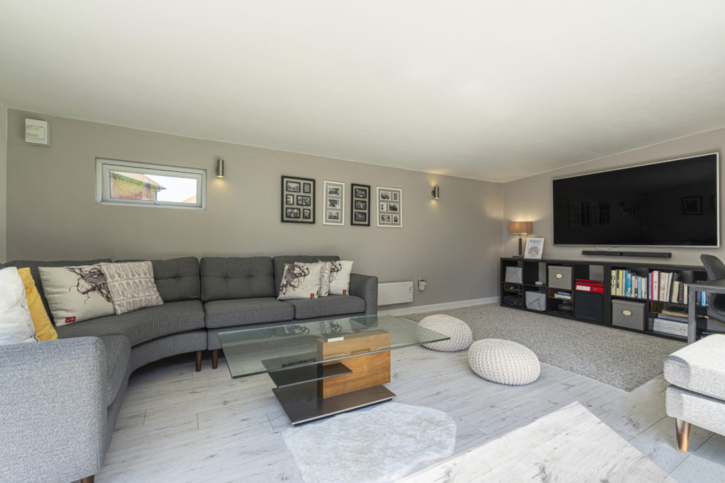Interior of a garden room with a grey L shaped sofa, coffee table and photos on the back wall