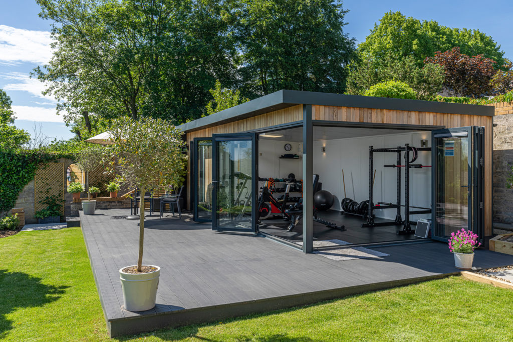 Exterior of a garden gym on a patio with a bistro set and umbrella outside and a tree in a pot