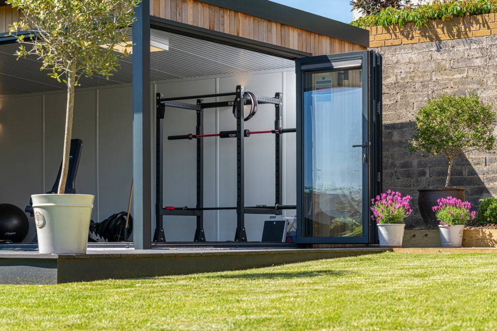 Exterior of a garden gym on a patio with a tree in a pot to the left. The doors are open, looking into gym equipment